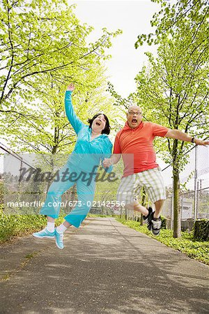 Couple jumping for joy outside Stock Photo - Premium Royalty-Free, Image code: 673-02142556
