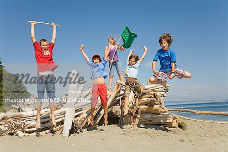 Group of children jumping at beach Stock Photo - Premium Royalty-Free, Image code: 673-02142810