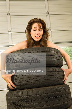 Nude woman standing in stack of tires Stock Photo - Premium Royalty-Free, Image code: 673-02142840