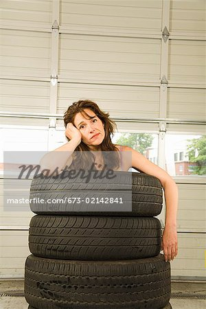 Nude woman standing in stack of tires Stock Photo - Premium Royalty-Free, Image code: 673-02142841