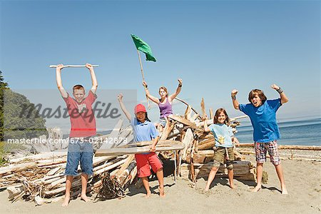Children cheering next to beach fort Stock Photo - Premium Royalty-Free, Image code: 673-02142878