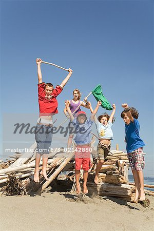 Children jumping next to beach fort Stock Photo - Premium Royalty-Free, Image code: 673-02142880