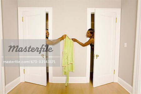 African couple handing clothing between dressing rooms Stock Photo - Premium Royalty-Free, Image code: 673-02143171