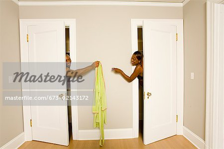 African couple handing clothing between dressing rooms Stock Photo - Premium Royalty-Free, Image code: 673-02143172