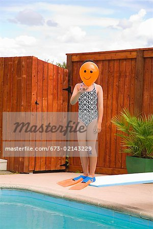 Girl with balloon in front of face over swimming pool Stock Photo - Premium Royalty-Free, Image code: 673-02143229