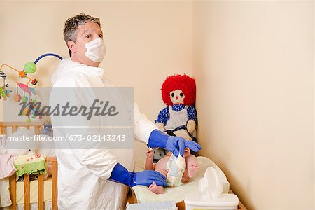 Father in decontamination suit changing baby's diaper Stock Photo - Premium Royalty-Free, Image code: 673-02143243