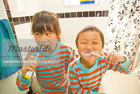 Asian siblings brushing teeth Stock Photo - Premium Royalty-Free, Image code: 673-02143877