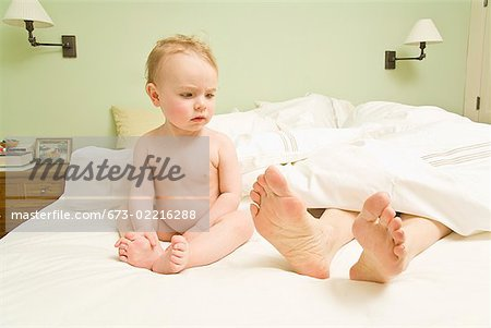 Curious baby looking at mother's feet in bed Stock Photo - Premium Royalty-Free, Image code: 673-02216288