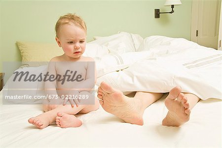 Curious baby looking at mother's feet in bed Stock Photo - Premium Royalty-Free, Image code: 673-02216289