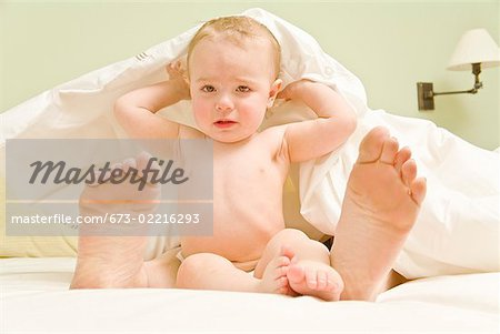 Sad baby and mother's feet under blanket in bed Stock Photo - Premium Royalty-Free, Image code: 673-02216293