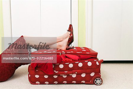 Woman in red dress resting on polka dot patterned suitcase Stock Photo - Premium Royalty-Free, Image code: 673-02216480