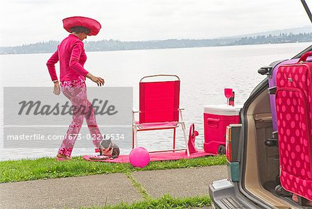 Woman in pink and Boston Terrier dog picnicking by bay Stock Photo - Premium Royalty-Free, Image code: 673-02216534