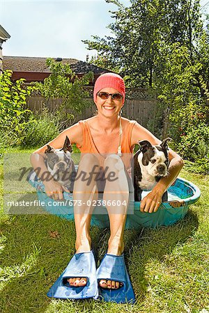 Woman sitting in a wading pool with two Boston Terriers Stock Photo - Premium Royalty-Free, Image code: 673-02386604