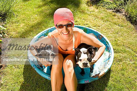 Woman sitting in a wading pool with two Boston Terriers Stock Photo - Premium Royalty-Free, Image code: 673-02386605
