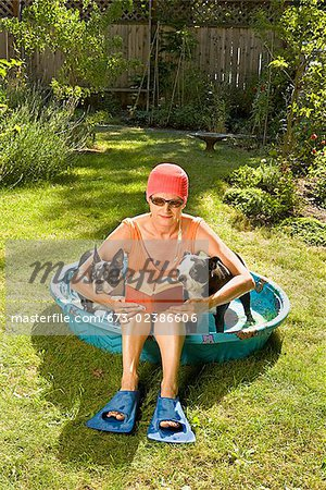 Woman reading a book in a wading pool between two Boston Terriers Stock Photo - Premium Royalty-Free, Image code: 673-02386606
