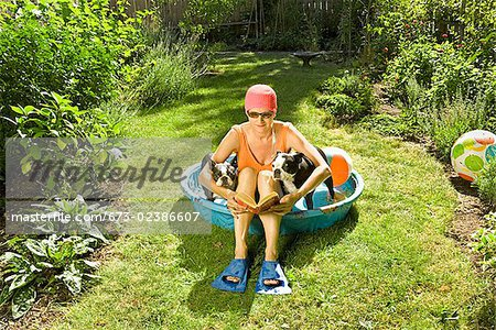 Woman reading a book in a wading pool between two Boston Terriers Stock Photo - Premium Royalty-Free, Image code: 673-02386607
