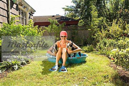 Woman sitting between two Boston Terriers in a wading pool Stock Photo - Premium Royalty-Free, Image code: 673-02386608