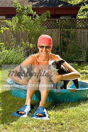 Woman sitting between two Boston Terriers in a wading pool Stock Photo - Premium Royalty-Free, Image code: 673-02386609