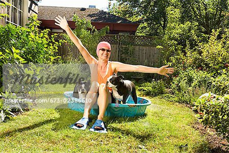 Woman sitting between two Boston Terriers in a wading pool Stock Photo - Premium Royalty-Free, Image code: 673-02386610
