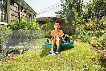 Woman sitting between two Boston Terriers in a wading pool Stock Photo - Premium Royalty-Free, Image code: 673-02386611