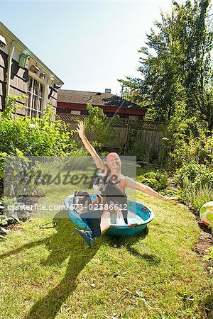 Woman sitting in a wading pool with two dogs Stock Photo - Premium Royalty-Free, Image code: 673-02386612