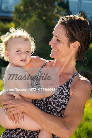 Woman carrying her baby girl Stock Photo - Premium Royalty-Free, Image code: 673-02386663