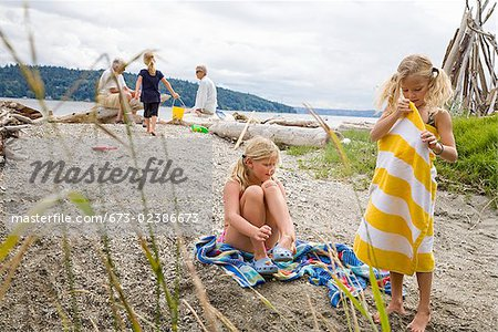 Two girls with their family on the beach Stock Photo - Premium Royalty-Free, Image code: 673-02386673