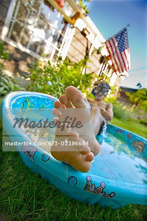 Boy wearing snorkel and lying in a wading pool Stock Photo - Premium Royalty-Free, Image code: 673-02386684