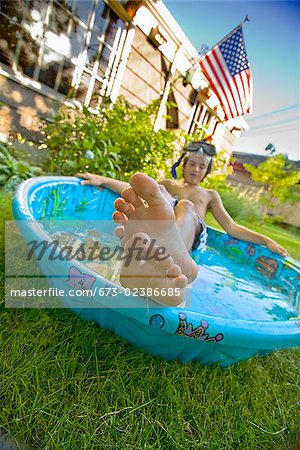 Boy wearing snorkel and lying in a wading pool Stock Photo - Premium Royalty-Free, Image code: 673-02386685