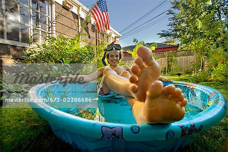 Boy wearing snorkel and lying in a wading pool Stock Photo - Premium Royalty-Free, Image code: 673-02386686