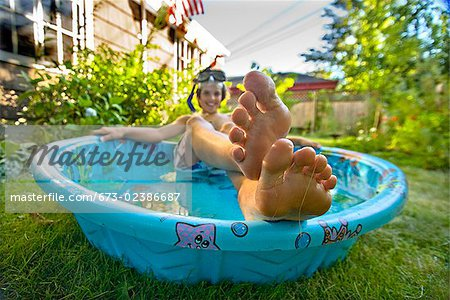 Boy wearing snorkel and lying in a wading pool Stock Photo - Premium Royalty-Free, Image code: 673-02386687