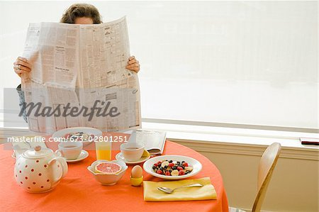 Woman at home having breakfast and reading newspaper Stock Photo - Premium Royalty-Free, Image code: 673-02801251