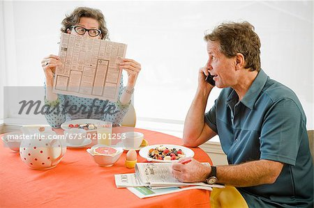 Couple having breakfast and checking newspaper classifieds Stock Photo - Premium Royalty-Free, Image code: 673-02801253