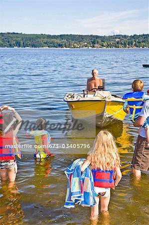 family wading out to motorboat Stock Photo - Premium Royalty-Free, Image code: 673-03405796