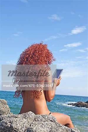 woman by sea with e-book Stock Photo - Premium Royalty-Free, Image code: 673-03623047