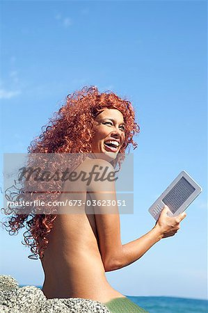 woman by sea with e-book Stock Photo - Premium Royalty-Free, Image code: 673-03623051
