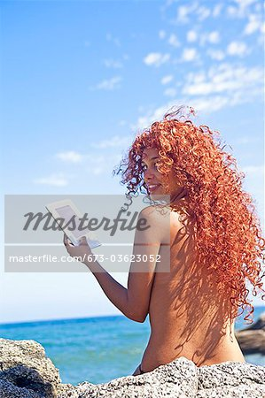 woman by sea with e-book Stock Photo - Premium Royalty-Free, Image code: 673-03623052