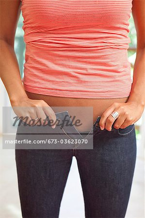 woman struggling to zip tight pants Stock Photo - Premium Royalty-Free, Image code: 673-03623070