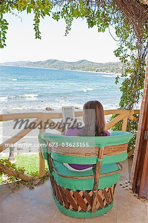 woman reading e-book on balcony Stock Photo - Premium Royalty-Free, Image code: 673-03623155