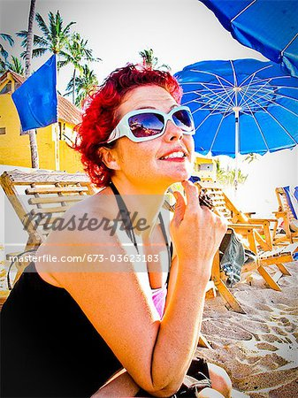 woman sitting at beach café Stock Photo - Premium Royalty-Free, Image code: 673-03623183