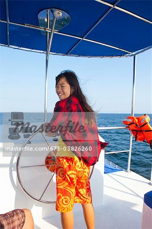 teen girl steering yacht Stock Photo - Premium Royalty-Free, Image code: 673-03826260