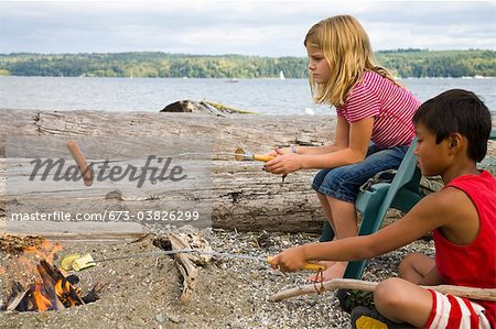 children roasting hotdogs over beach fire Stock Photo - Premium Royalty-Free, Image code: 673-03826299