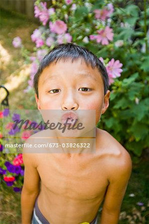 asian boy with puckered lips outdoors Stock Photo - Premium Royalty-Free, Image code: 673-03826322