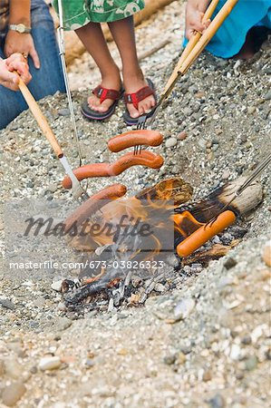 hot dogs roasting over beach fire Stock Photo - Premium Royalty-Free, Image code: 673-03826323
