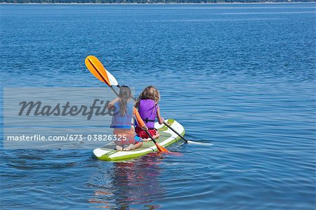 girls on paddle board in lake Stock Photo - Premium Royalty-Free, Image code: 673-03826325