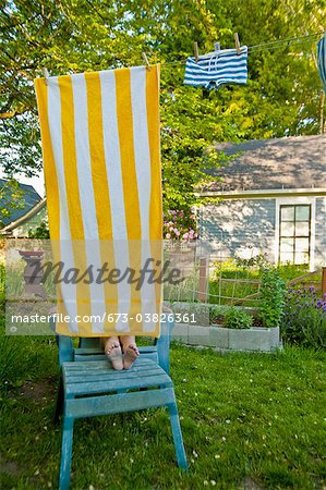 boy on garden chair under beach towel Stock Photo - Premium Royalty-Free, Image code: 673-03826361