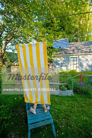 boy on garden chair under beach towel Stock Photo - Premium Royalty-Free, Image code: 673-03826362