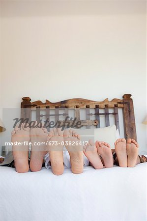 family lying on bed, feet lined up Stock Photo - Premium Royalty-Free, Image code: 673-03826417