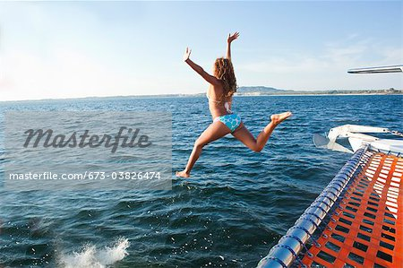 woman jumping off yacht into sea Stock Photo - Premium Royalty-Free, Image code: 673-03826474