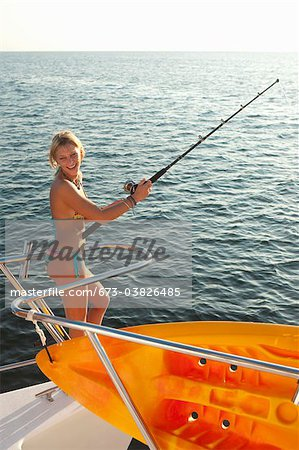 young woman with fishing pole on yacht Stock Photo - Premium Royalty-Free, Image code: 673-03826485